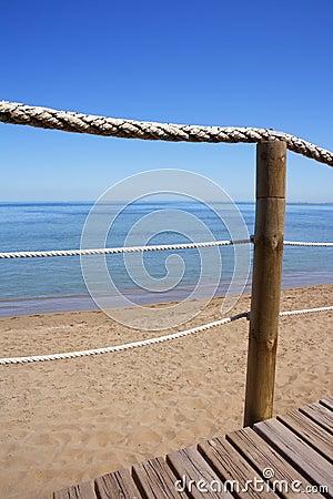 Catwalk on wood rope railing on sea beach