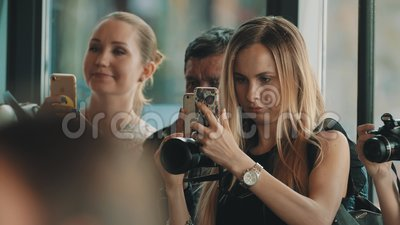Women and man group filming with cameras and smart phones at crowded event. Caucasian adult women and man group filming and taking pictures with cameras and stock video
