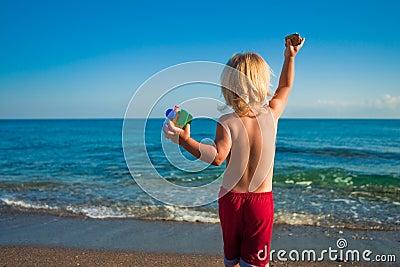 Caucasian baby boy throw stones to the sea