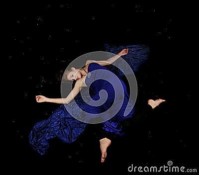 Caucasian beauty in blue dress floating in black