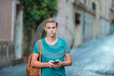 Caucasian boy is holding cellphone outdoors on the street. Man using mobile smartphone. Stock Photo