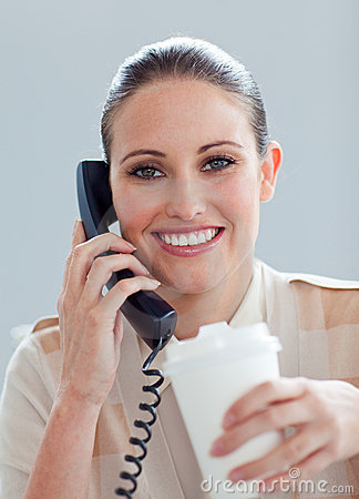 Caucasian businesswoman on phone drinking a coffee