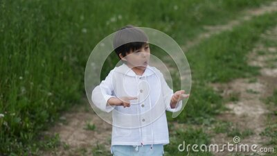 Caucasian child boy in a white sweater with a hood dancing on the road stock video footage