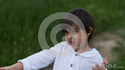 Caucasian child boy in a white sweater with a hood dancing on the road stock video