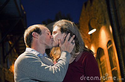 Caucasian couple kissing in brick alley way