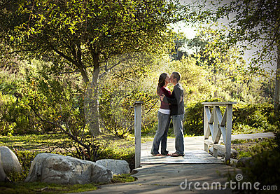 Caucasian couple kissing on outdoor wooden bridge