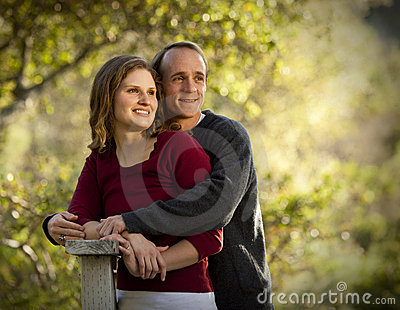 Caucasian couple in love on outdoor wooden bridge