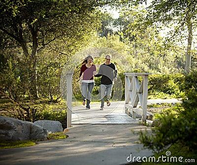 Caucasian couple running on outdoor wooden bridge