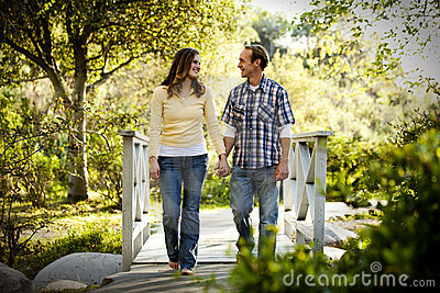 Caucasian couple walking on outdoor wooden bridge