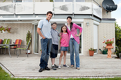 Caucasian family standing in front of house
