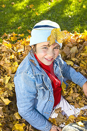 Caucasian female child playing in autumn leaves