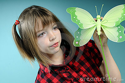 Caucasian girl showing butterfly toy