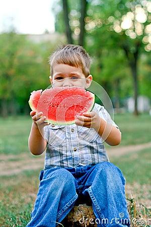 Caucasian little boy eats a slice of watermelon