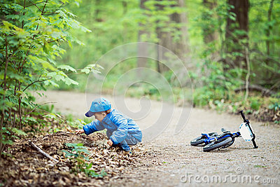 Caucasian little boy toddler in blue jacket, jeans and baseball cap with bike in park playground outside, sitting on ground Stock Photo