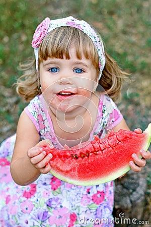 Caucasian little girl eats a slice of watermelon