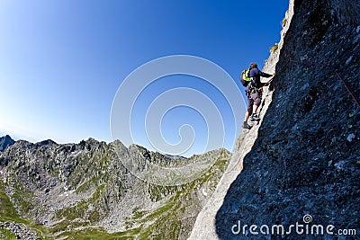 Caucasian male climber climbing a steep wall