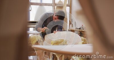 Caucasian male surfboard maker working in his studio and making a wooden surfboard stock video footage