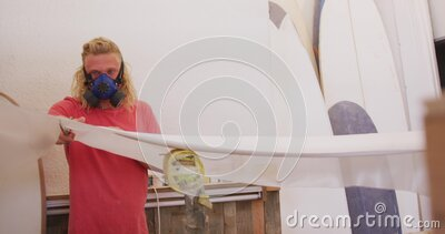 Caucasian male surfboard maker wearing a face mask and making a surfboard stock footage