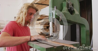 Caucasian male surfboard maker working in his studio and making a wooden surfboard stock video