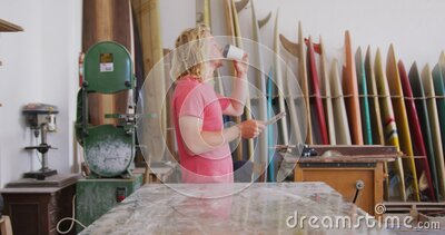 Caucasian male surfboard makers using his smartphone and drinking coffee stock footage