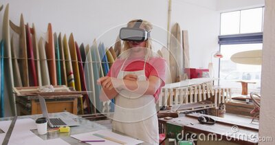 Caucasian male surfboard makers wearing a VR headset stock video