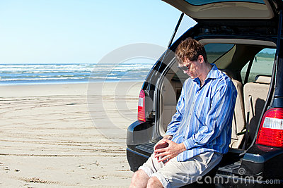 Caucasian man in car at beach, unhappy, worried expression