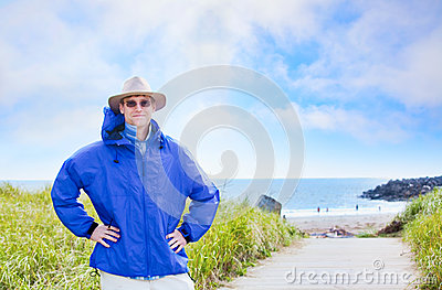 Caucasian man in forties wearing rain jacket by ocean shore