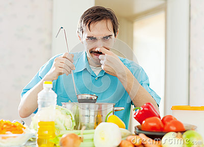 Caucasian man holding  nose because of bad smell