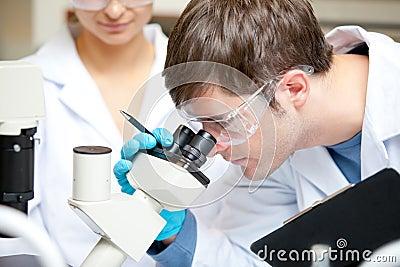Caucasian scientist looking through a microscope