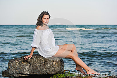 Caucasian teen girl in bikini and white shirt lounging on lava rocks by the ocean