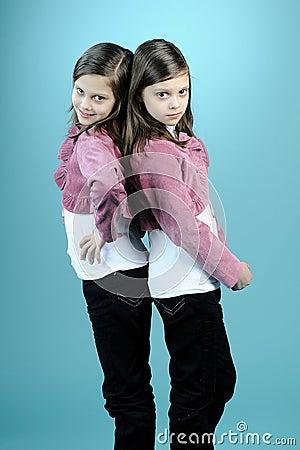 Caucasian twins posing in studio