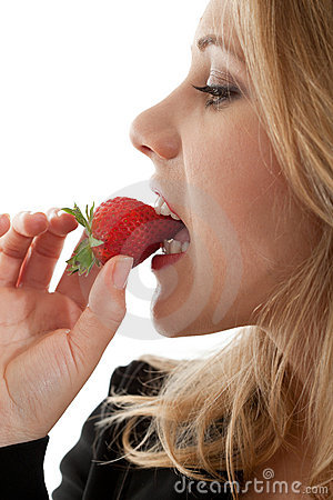 Caucasian woman biting strawberry