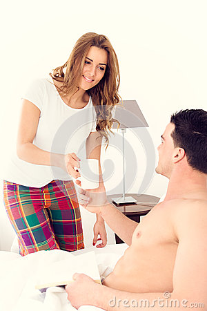 Caucasian woman carrying coffee to her boyfriend in bed Stock Photo