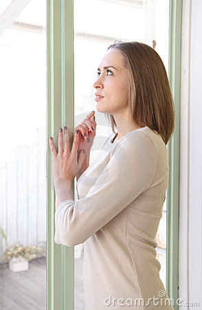 Caucasian woman standing by the window