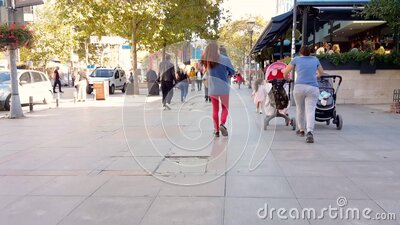 Caucasian woman with two baby strollers taking a walk in Bagdat Street at the weekend. Istanbul, Turkey - October 05, 2018: Back view of a Caucasian woman stock video
