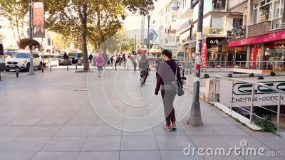 Caucasian woman walking alone near stores in Bagdat Street at the weekend. Istanbul, Turkey - October 05, 2018: Back view of a young Caucasian brunette woman in stock footage