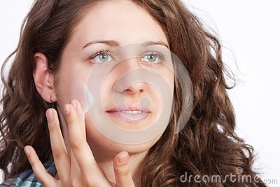 Caucasian young woman applying moisture