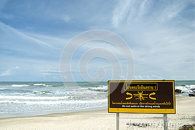 Caution sign on white sand beach