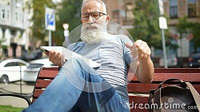 Cavalheiro superior avançado que relaxa no banco com portátil filme