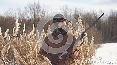 Cazador alegre feliz que sostiene un rifle y que mira a un lado almacen de video