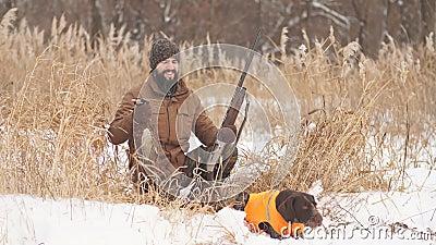 Cazador cansado y su perro que tienen un resto en un día de invierno frío almacen de video