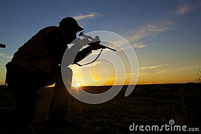 Cazador del rifle en salida del sol