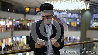 Celebrazione dell'uomo d'affari il suo successo mentre esaminando un telefono cellulare video d archivio