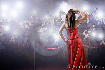 Celebrity posing with paparazzi