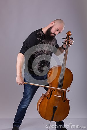 Cellist playing classical music on cello. bearded man fooling around with a musical instrument Stock Photo