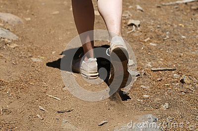 Centered close up of woman s feet hiking in dirt