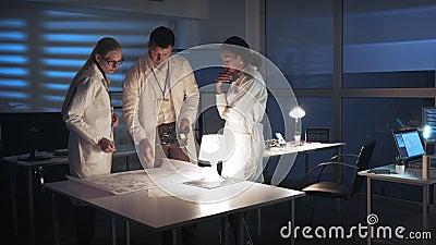 Centro de investigación de la tecnología: Ingenieros de desarrollo multirraciales de electrónica en las capas blancas que trabaja almacen de metraje de vídeo