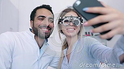 Centro do olho Mulher que faz a foto no telefone com doutor On Eye Exam filme
