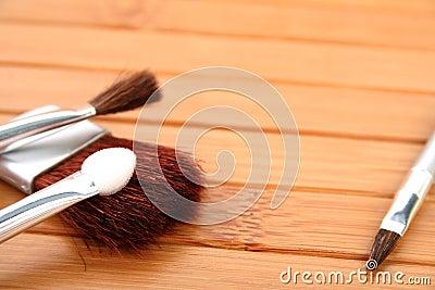Cepillos del maquillaje en la madera