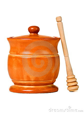 Ceramic jar with honey and wooden stick